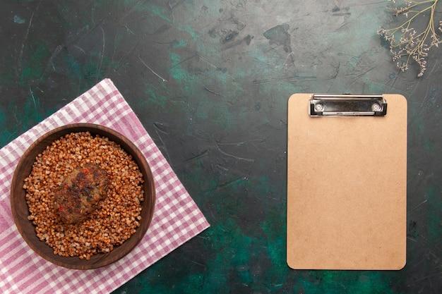 Draufsicht köstlicher gekochter buchweizen mit schnitzel und notizblock auf dunkelgrüner oberflächenzutat mahlzeitlebensmittelgemüsegericht