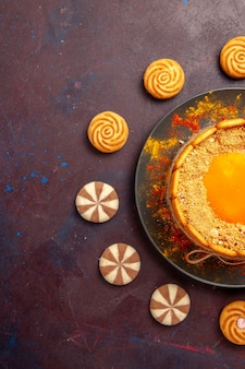 Draufsicht köstlicher gelber kuchen cremiges dessert mit keksen auf dem dunklen schreibtisch