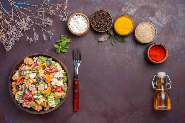 Draufsicht köstlicher gemüsesalat mit verschiedenen gewürzen auf dunkelviolettem hintergrund gesundheitsdiät-gemüsesalat-mittagessen
