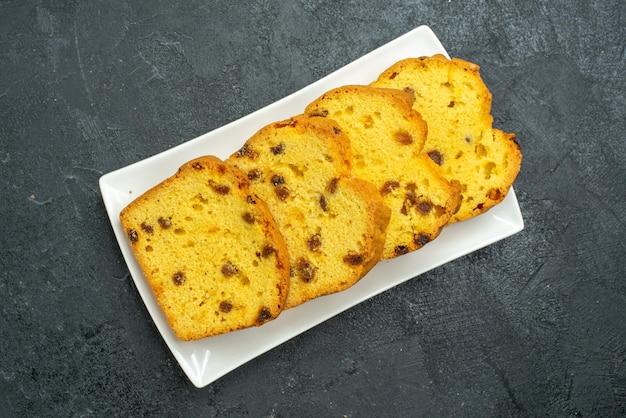 Draufsicht köstlicher geschnittener kuchen in der platte auf der dunklen oberfläche süßer kuchenkeks-teekuchentee