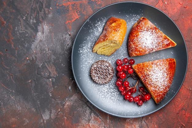 Draufsicht köstlicher geschnittener kuchen mit roten beeren auf dem dunklen kuchen des dunklen tischkuchens