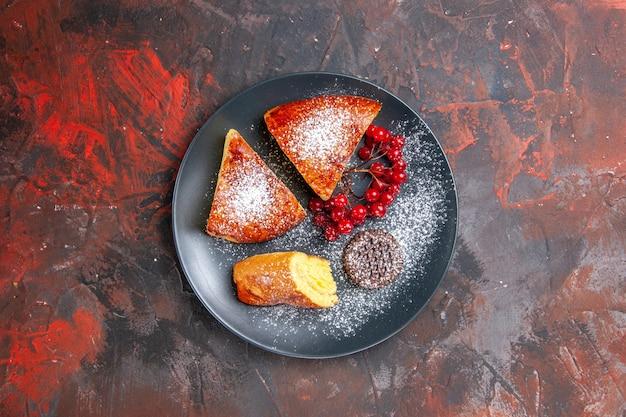 Draufsicht köstlicher geschnittener kuchen mit roten beeren auf dem dunklen tisch süßer kuchenkuchen