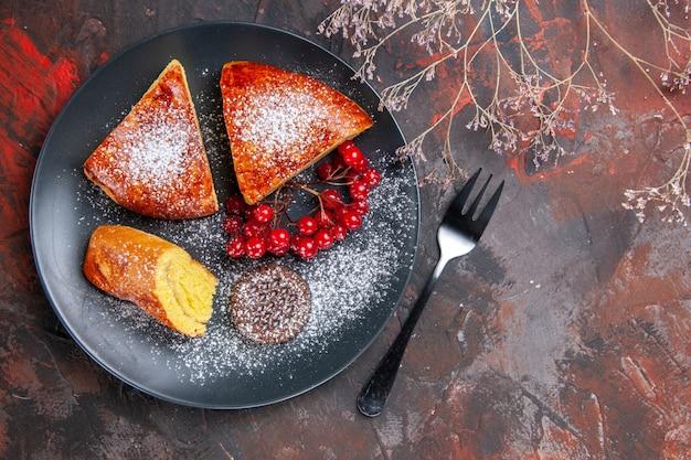 Draufsicht köstlicher geschnittener kuchen mit roten beeren auf dunklem kuchen des dunklen tischkuchens