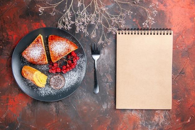 Draufsicht köstlicher geschnittener kuchen mit roten beeren auf dunklen kuchen des dunklen tischkuchens