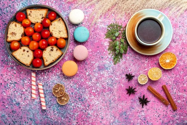 Draufsicht köstlicher geschnittener kuchen mit sauren frischen pflaumen französischen macarons und einer tasse tee auf dem rosa schreibtisch