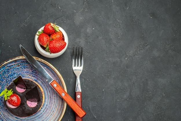 Draufsicht köstlicher käsekuchen mit erdbeere ein messer auf tellerschüssel mit erdbeeren eine gabel auf dunklem, isoliertem hintergrund