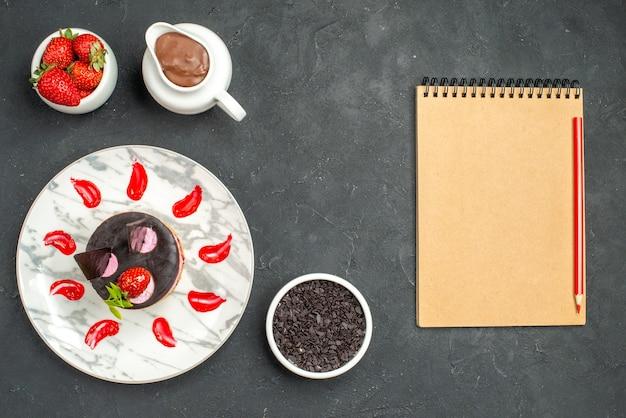 Draufsicht köstlicher käsekuchen mit erdbeere und schokolade auf ovaler tellerschüssel mit erdbeeren und schokolade ein notizbuch auf dunklem, isoliertem hintergrund