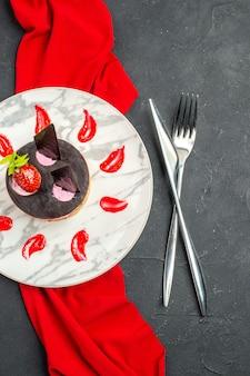 Draufsicht köstlicher käsekuchen mit erdbeere und schokolade auf teller mit rotem schal, gekreuztem messer und gabel auf dunklem, isoliertem hintergrund