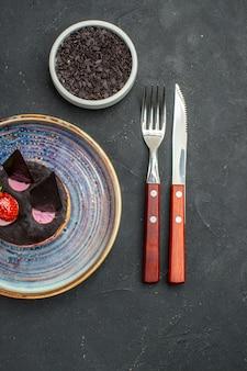Draufsicht köstlicher käsekuchen mit erdbeere und schokolade auf tellerschüssel mit schokoladengabel und -messer auf dunklem, isoliertem hintergrund