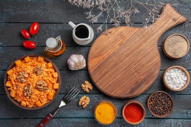 Draufsicht köstlicher karottensalat mit walnüssen und gewürzen auf dunkelblauem schreibtisch nussdiätsalat farbe gesundheit
