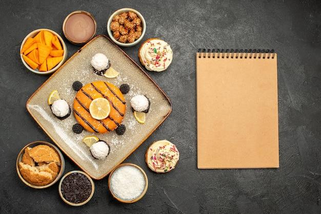 Draufsicht köstlicher kleiner kuchen mit kokosbonbons auf dunkelgrauem hintergrund kuchen dessert keks kuchen keks tee