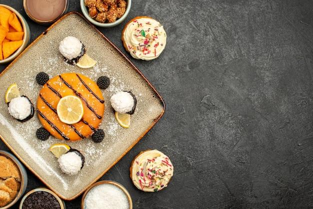 Draufsicht köstlicher kleiner kuchen mit kokosbonbons auf einem dunkelgrauen hintergrund kuchendessertkeksplätzchenteekuchen