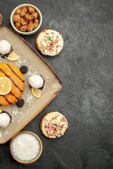Draufsicht köstlicher kleiner kuchen mit kokosbonbons auf einem dunkelgrauen oberflächenteekuchen-keks-dessert