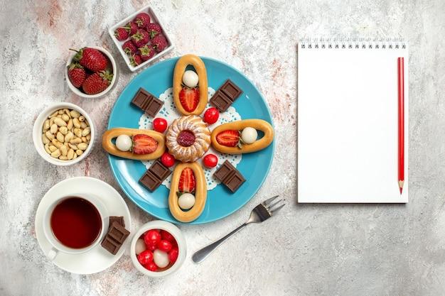 Draufsicht köstlicher kleiner kuchen mit schokoriegeln tee und süßen crackern auf weißem hintergrund cracker süße kekskuchenkuchen schokolade