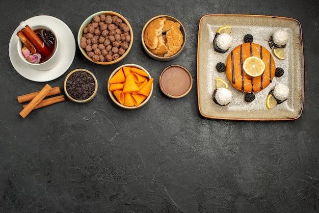 Draufsicht köstlicher kleiner kuchen mit tasse tee auf dunklem hintergrund süßigkeitskekskuchenkuchenplätzchen süß