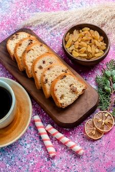 Draufsicht köstlicher kuchen geschnittener kuchen mit rosinen und mit tasse kaffee auf rosa oberfläche backen kuchen zucker süßer kekskeks