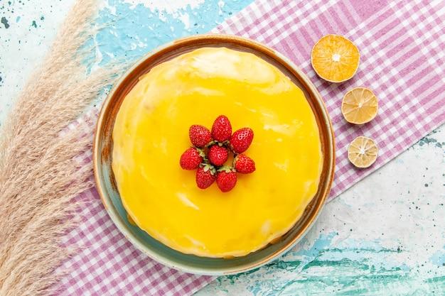 Draufsicht köstlicher kuchen mit gelbem sirup und frischen roten erdbeeren auf der hellblauen oberfläche kekskuchen backen süßen zuckertorten-tee