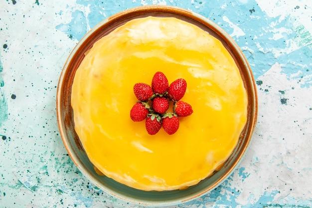Draufsicht köstlicher kuchen mit gelbem sirup und roten erdbeeren auf der blauen oberfläche kekskuchen backen süßen kuchenzuckertee