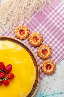 Draufsicht köstlicher kuchen mit gelben sirup frischen roten erdbeeren und keksen auf blauem schreibtischkekskuchen backen süßen zuckertorten-tee