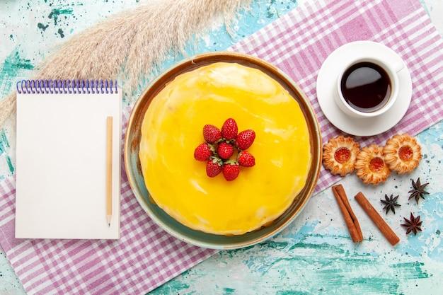 Draufsicht köstlicher kuchen mit gelben sirup frischen roten erdbeeren und tasse tee auf blauer oberfläche kekskuchen backen süße zuckerkuchen