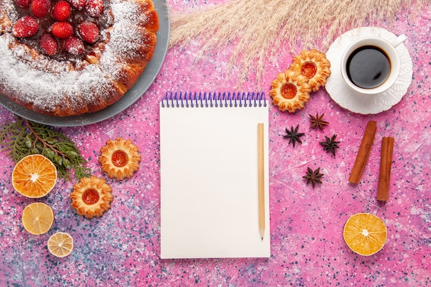 Draufsicht köstlicher kuchen mit notizblock und tee auf rosa schreibtischkuchenzuckersüßbackkeksfarbe