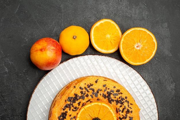 Draufsicht köstlicher kuchen mit orangenscheiben auf der dunklen oberfläche obstdessertkuchenkuchen keks tee
