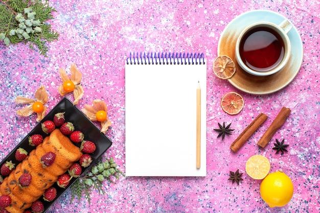Draufsicht köstlicher kuchen mit roten frischen erdbeeren mit tee auf rosa schreibtisch.