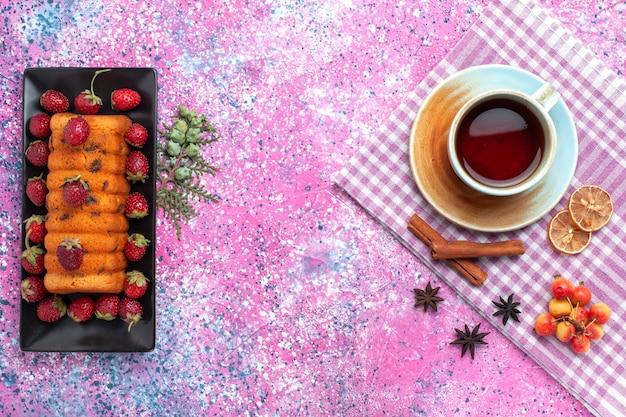 Draufsicht köstlicher kuchen mit roten frischen erdbeeren und tee auf dem rosa hintergrund.