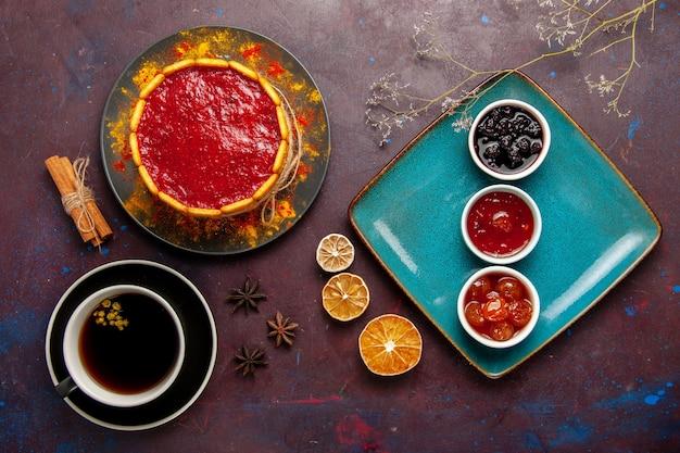 Draufsicht köstlicher kuchen mit roten sahne-marmeladen und tasse kaffee auf dunkler oberfläche kekskuchen zuckerdessertkuchen süße kekse