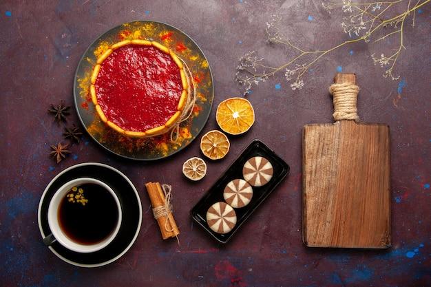 Draufsicht köstlicher kuchen mit roten sahnekeksen und tasse kaffee auf dem dunklen schreibtischkekskuchenzuckerdessertkuchen süßer keks