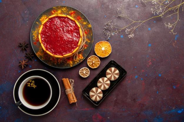 Draufsicht köstlicher kuchen mit roten sahnekeksen und tasse kaffee auf dunklem hintergrund kekskuchen zuckerdessertkuchen süße kekse