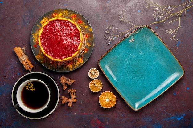 Draufsicht köstlicher kuchen mit roter sahne und kaffee auf dem dunklen hintergrundkekskuchenzuckerdessertkuchen süße kekse