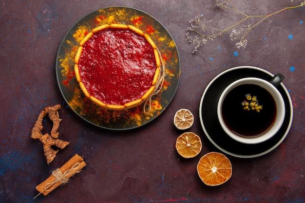 Draufsicht köstlicher kuchen mit roter sahne und tasse kaffee auf den dunklen hintergrundkekskuchen-zuckerdessertkuchen-süßen keksen