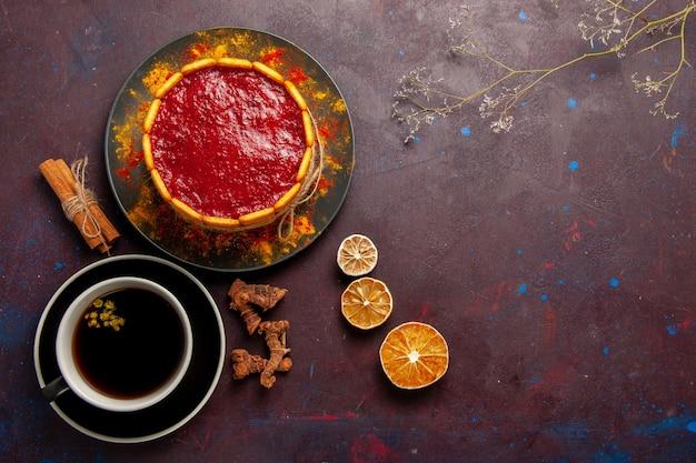 Draufsicht köstlicher kuchen mit roter sahne und tasse kaffee auf dunklem schreibtischkekskuchenzuckerdessertkuchen süße kekse