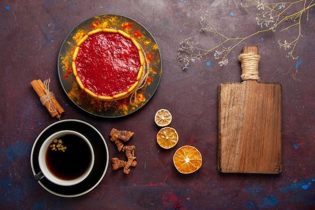 Draufsicht köstlicher kuchen mit roter sahne und tasse kaffee auf dunklem schreibtischkekskuchenzuckerdessertkuchen süßer keks