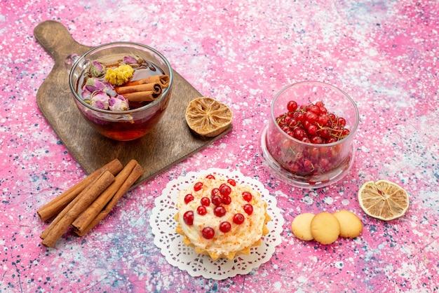 Draufsicht köstlicher kuchen mit sahne und roten preiselbeeren zusammen mit zimt und einer tasse tee auf dem hellen schreibtischkuchen