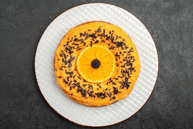 Draufsicht köstlicher kuchen mit schokoladenstückchen und orangenscheiben auf dem dunklen oberflächenkuchen dessertkuchen tee fruchtkeks