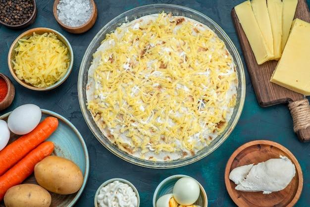 Draufsicht köstlicher mayyonaised salat zusammen mit frischem gemüse und käse auf dunkelblauem hintergrund.