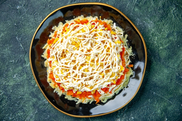 Draufsicht köstlicher mimosensalat mit eiern kartoffel und huhn innerhalb platte auf dunkelblauem hintergrund