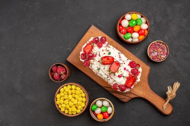 Draufsicht köstlicher obstkuchen mit früchten und süßigkeiten auf dunklem hintergrund kuchenplätzchen süßer kekskuchentee
