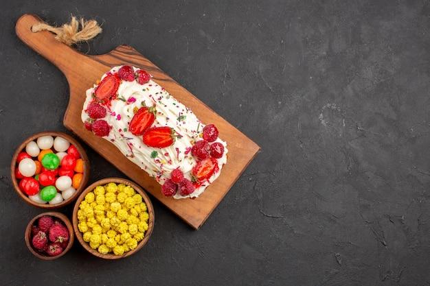 Draufsicht köstlicher obstkuchen mit sahne und bonbons auf dem dunklen hintergrund süßigkeitskuchen keks-frucht-süßkuchen