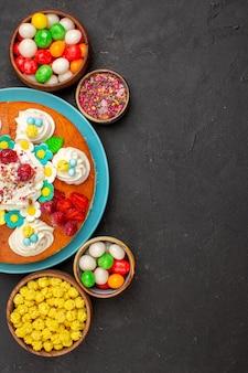 Draufsicht köstlicher obstkuchen mit süßigkeiten auf dunklem hintergrund kuchenplätzchen süßer kekskuchentee
