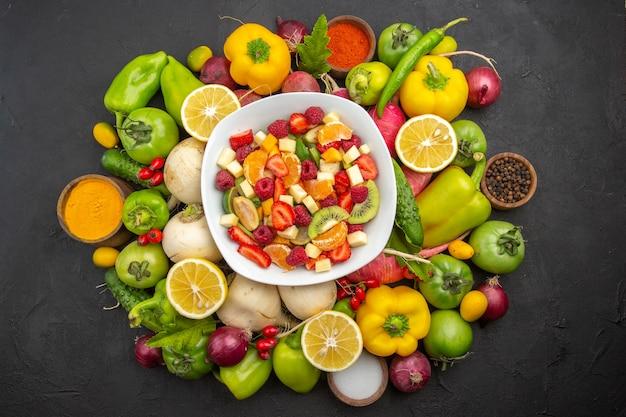 Draufsicht köstlicher obstsalat im teller mit frischen früchten auf grauem obstbaum exotische tropische fotoreife diät ripe