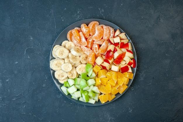 Draufsicht köstlicher obstsalat in scheiben geschnittene mandarinen äpfel bananen und orangen auf dunklem hintergrund