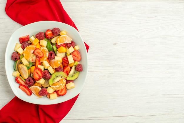 Draufsicht köstlicher obstsalat mit rotem gewebe auf weißem exotischen fruchtigen beerenzitrusfrüchten reifen ausgereiften fotofreiraum