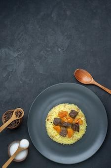 Draufsicht köstlicher pilaw gekochter reis mit fleischscheiben und gewürzen auf dunkler oberfläche