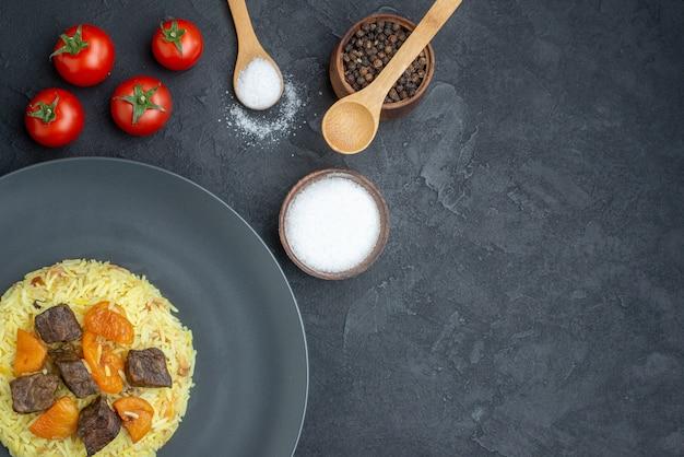 Draufsicht köstlicher pilaw gekochter reis mit fleischscheiben und tomaten auf dunkler oberfläche