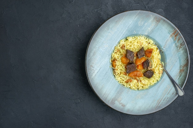 Draufsicht köstlicher pilaw gekochter reis mit getrockneten aprikosen und fleischscheiben innerhalb platte auf dunkler oberfläche