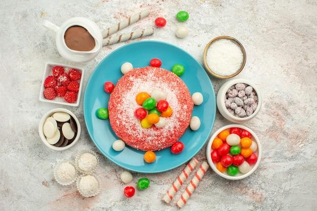 Draufsicht köstlicher rosa kuchen mit bunten bonbons und keksen auf weißer oberflächenregenbogenfarbendessertkuchensüßigkeit