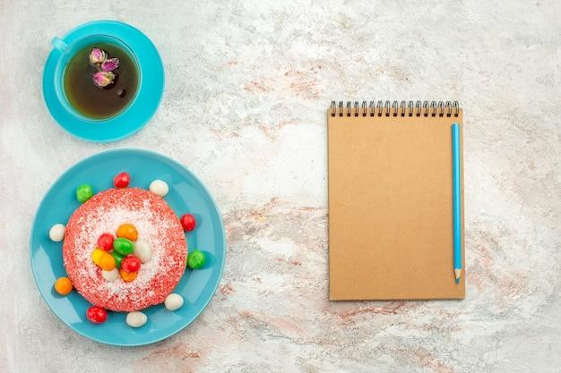Draufsicht köstlicher rosa kuchen mit bunten bonbons und tasse tee auf weißer oberfläche kuchen regenbogenfarben kuchen dessert süßigkeiten